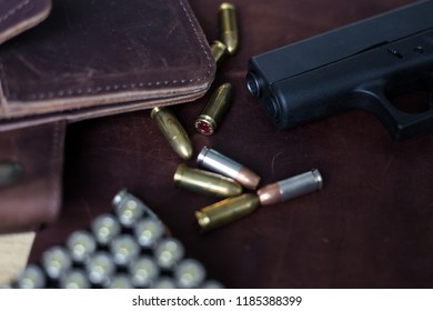 9mm Sub compact everday carry modern gun with bullet on leather background, Pocket gun