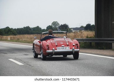 9th of August 2014 - Scene from a Danish highway with close up of a vintage red MG passing under a bridge, Aalborg, Denmark