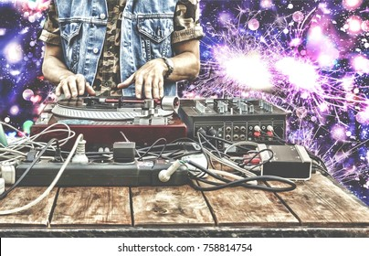 9th of March. World Day DJ. DJ playing music at mixer closeup. DJ at the remote in a nightclub, onprivate party or on the beach on the background of festive fireworks, salute, colorful lights, bokeh