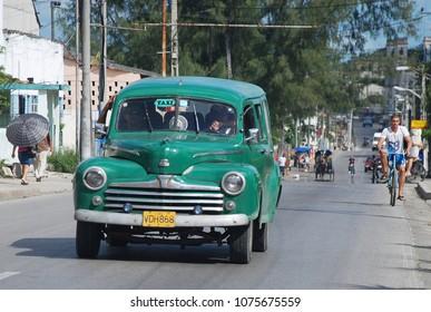 9th of November 2013 - Scene from busy Cuban  streeet with vintage green taxi, Santa Clara, Cuba