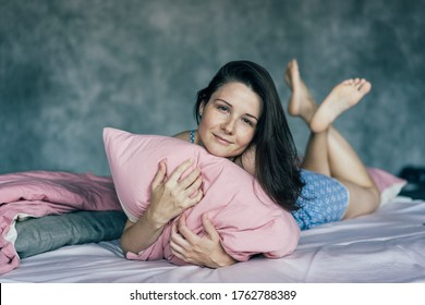 .A cute Caucasoid girl lies in her pajamas in bed and hugs a pillow. Morning awakening and lazy rest.