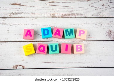 """""""a damp squib""""-the words on wooden cubes.  A background image of english words on colorful building blocks."""