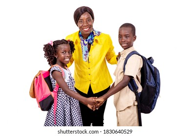 .a female teacher in a yellow shirt standing on a white background with two elementary school students looking at the camera smiling.