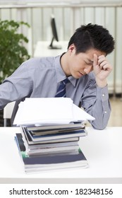 A man looks stressed as he works at his desk
