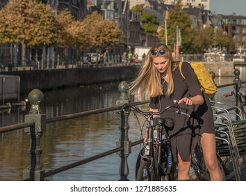 .A young, beautiful girl parks her bike in the parking lot. The ancient city of Mechelen. Belgium October 13, 2018. Cityscape.
