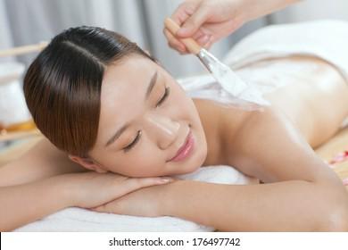 A young lady enjoy body mask in spa salon