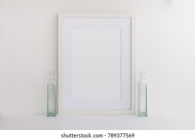 A4 A3 A5 white wooden empty photo frame with empty space for your own overlay.  Perfect for blogger or website designer for light minimal feminine branding. Frame standing next to glass bottles.