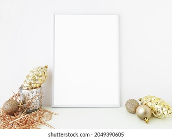 A4 white photo frame in christmas concept. Gold composition made with decorative gold ornaments and baubles on a white background. Vertical frame mockup. Home decor. For lettering and art design.