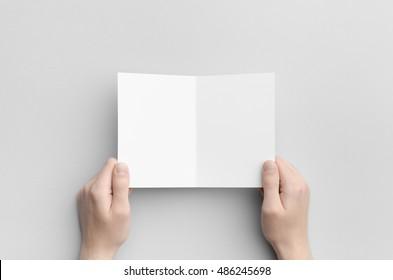 A6 Bi-Fold / Half-Fold Brochure Mock-Up - Male hands holding a blank bi-fold on a gray background.