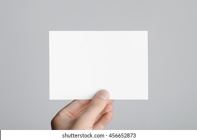 A6 Flyer / Postcard / Invitation Mock-Up - Male hands holding a blank flyer on a gray background.