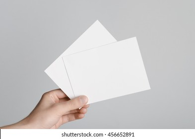 A6 Flyer / Postcard / Invitation Mock-Up - Male hands holding blank flyers on a gray background.