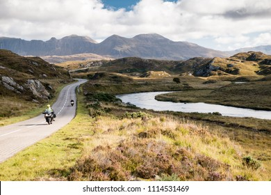 The A837 road, part of the North Coast 500 route, meanders past rivers and low hills in the glacial landscape of Assynt, with Quinag mountain in the distance, in the Northwest Highlands of Scotland.