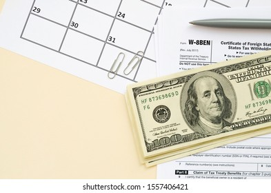 aaaaaForm W-8BEN Certificate of foreign status of beneficial owner for United States tax withholding and reporting for individuals blank lies with pen and hundred dollar bills on calendar page