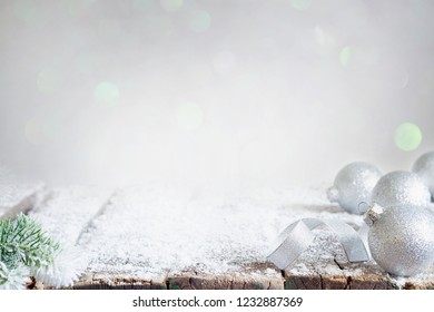 Aabstract christmas background with silver baubles and fir on empty snowy table