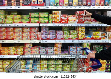 AACHEN, GERMANY - AUGUST 12, 2017: Aisle with a major assortment tea packings in a REAL Hypermarket containing Teekanne brand and REAL Store brand tea cartons.
