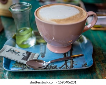 Aachen, Germany – December 07 2019. Close up of a cup of frothy coffee on a serving tray with tea spoon, complimentary biscuit and glass of mint water captured in a traditional German café