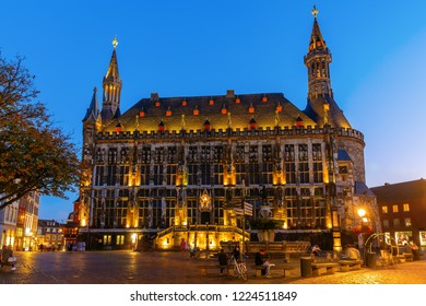 Aachen, Germany - October 15, 2018: Aachen city hall with unidentified people at night. The historical building dated from 1330. As before it is today the seat of the mayor of Aachen