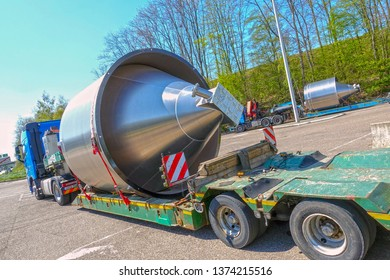 AACHEN, NRW, GERMANY - April 18, 2019: Heavy haulage of a big stainless steel container on a special low-loader trailer truck, parking road sight on a highway.