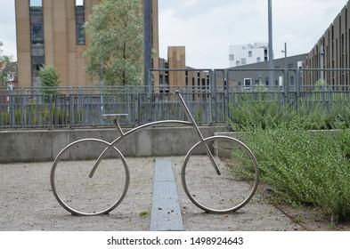 Aalborg / Denmark - July 29 2019: A designer modern unusual bike / bicycle parking stand in form of a simple metallic bike
