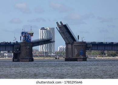 Aalborg, Denmark - July 7th 2020: The Limfjord bridge (Limfjordsbroen) opens for ship traffic, showing the building The Horizon (Horisonten) - the tallest building in Northern Jutland