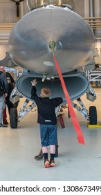 AALBORG, DENMARK - JUNE 10, 2018: Boy standing close to a F-16 on display at Danish Airshow 2018, June 10, 2018, Aalborg Airbase, Aalborg, Denmark.