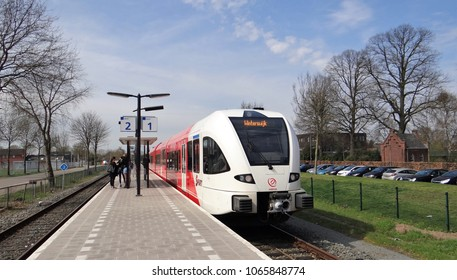 Aalten / Netherlands - April 10 2018: Arriva GTW diesel train drive by the small station of the dutch village Aalten in the Achterhoek. The destination of the red and white train is Winterswijk.