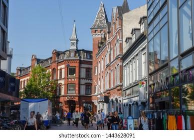 Aarhus, Denmark - 19 June 2019: people walking in front of an old traditional buildings at Aarhus in Denmark