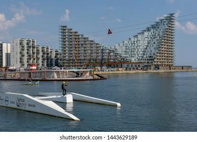 Aarhus, Denmark - 19 June 2019: man wakeboarding in front of modern residential neighborhood at Aarhus in Denmark