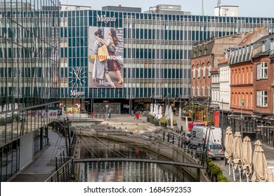 aarhus, Denmark - 24 march 2020:  Promenade along the river Aarhus A in the city center of the town of Aarhus. Stores and offices on both sides, Magasin Shopping center in the background