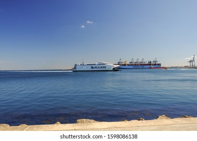 Aarhus, Denmark - circa august, 2019: Ferry boat arriving in the city port of the second largest city of the country. Maersk line ship in the background. Blue sky. Blue and bright sea's water.