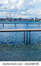"Aarhus / Denmark - June 22 2019: Circular infinite bridge in Aarhus, Denmark called ""Den Uendelige Bro"" with the skyline of the city in the background during a summer day."