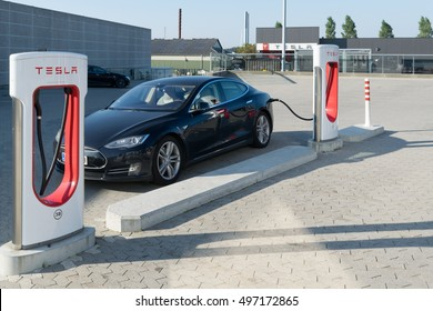 Aarhus, Denmark - September 14, 2016: Black Tesla car being charged at supercharger charging station. Superchargers are free connectors that charge Model S in minutes.