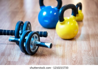 Ab roller wheel and kettlebells used for exercising abdominal muscles, on floor in ygm