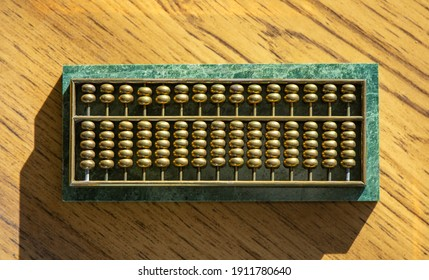 Abacus with brass beads mounted on a base of green malachite