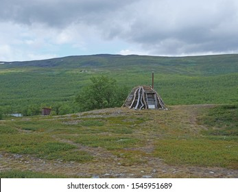Abadoned Sami hut Goathi in green hills landscape of Abisko National Park. Goahti is Lappish traditional dwelling made from fabric, peat moss and timber. Lapland, Northern Sweden on Kungsleden trail