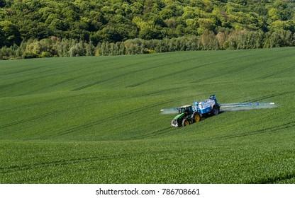 Abaliget, Baranya / Hungary - 05.02.2017: A farmer spraying on the spring wheat field with a John Deere tractor and a mamut topline sprayer.