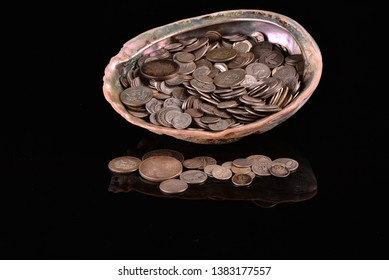 An abalone shell full of overflowing out of use real silver coins.