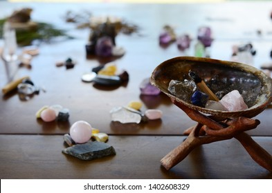 Abalone Shell with Palo Santo, and filled with healing crystals. Rose Quartz, Smokey Quartz, Sodalite, and Clear Quartz.  Burning palo santo in a abalone shell, being held. Variety of crystals shell