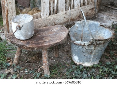 abandoned barn an old broken bucket and an aluminum pan on the wooden stool that was used by the farmer