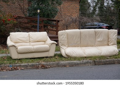 Abandoned beige couches on the grass by a curb in front of a house waiting to be removed on trash day