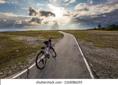 An abandoned bicycle parked on the cycling track. The sun produces amazing light rays in the sky. The image is simple and breathtaking. This image is suitable for background use or add quote above.
