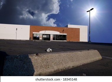 Abandoned Big-Box Store.  Focus on Parking Block in Foreground.