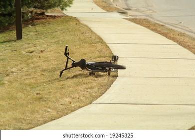 An abandoned bike lies near a sidewalk.
