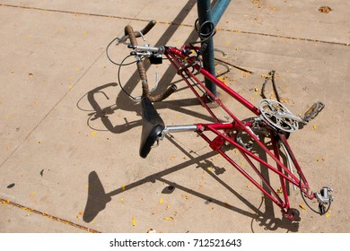 An abandoned bike without wheels still chained to a post on the street