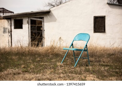 Abandoned blue metal folding chair in front of dilapidated house
