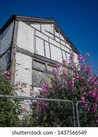 An abandoned and boarded up muck tudor building with pink flowers growing in front.