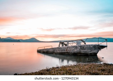 Abandoned boat in a lake. Sunset photo
