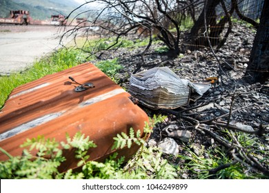 Abandoned book and radiator in burned area along train track with weeds and grass growing around them