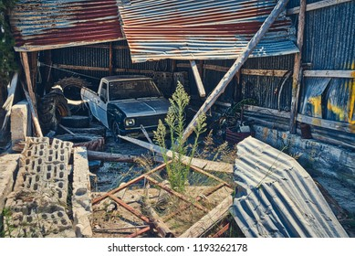 abandoned broken garage out of corrugated iron, with old car