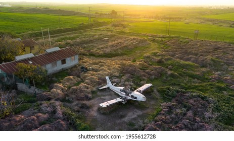 Abandoned broken plane in a field in countryside during sunset, aerial view